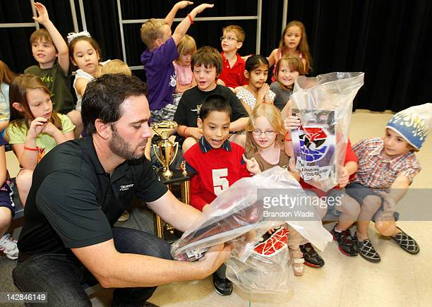 Jimmie Johnson hands out gift bags to students from Kari Abrams first grade class during an awards ceremony for the 'Speeding to Read' program at...