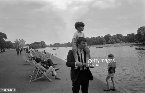 Jimmie Nicoll one time backup drummer for The Beatles strolling around Hyde Park with his son Howard on his shoulders London June 16th 1964