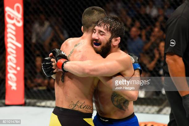 Jimmie Rivera and Thomas Almeida of Brazil embrace after finishing three rounds in their bantamweight bout during the UFC Fight Night event inside...