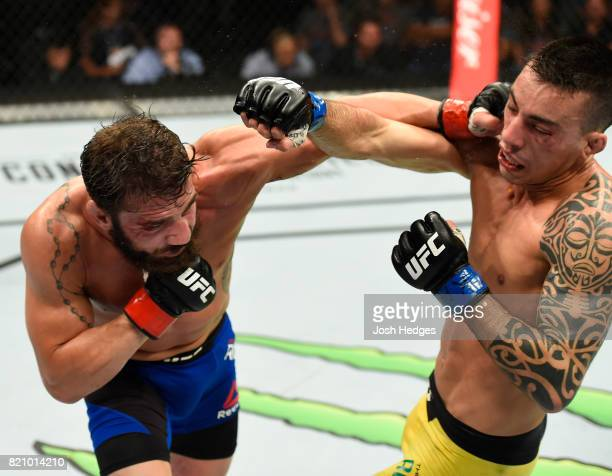 Jimmie Rivera punches Thomas Almeida of Brazil in their bantamweight bout during the UFC Fight Night event inside the Nassau Veterans Memorial...