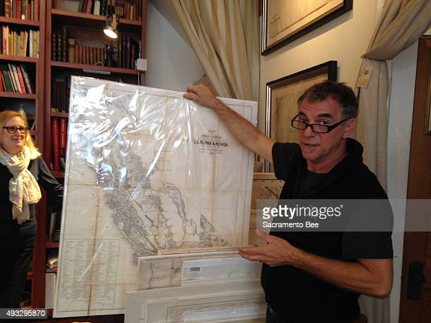 Jimmie Schein holds up a mid1800s map of Northern California with the Sierra Nevada mountain range yet to be charted