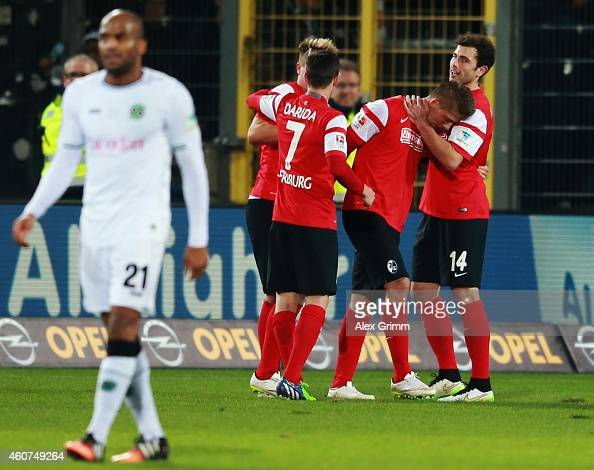 Jimmy Briand of Hannover reacts as Mike Frantz of Freiburg celebrates his team's first goal with team mates during the Bundesliga match between SC...