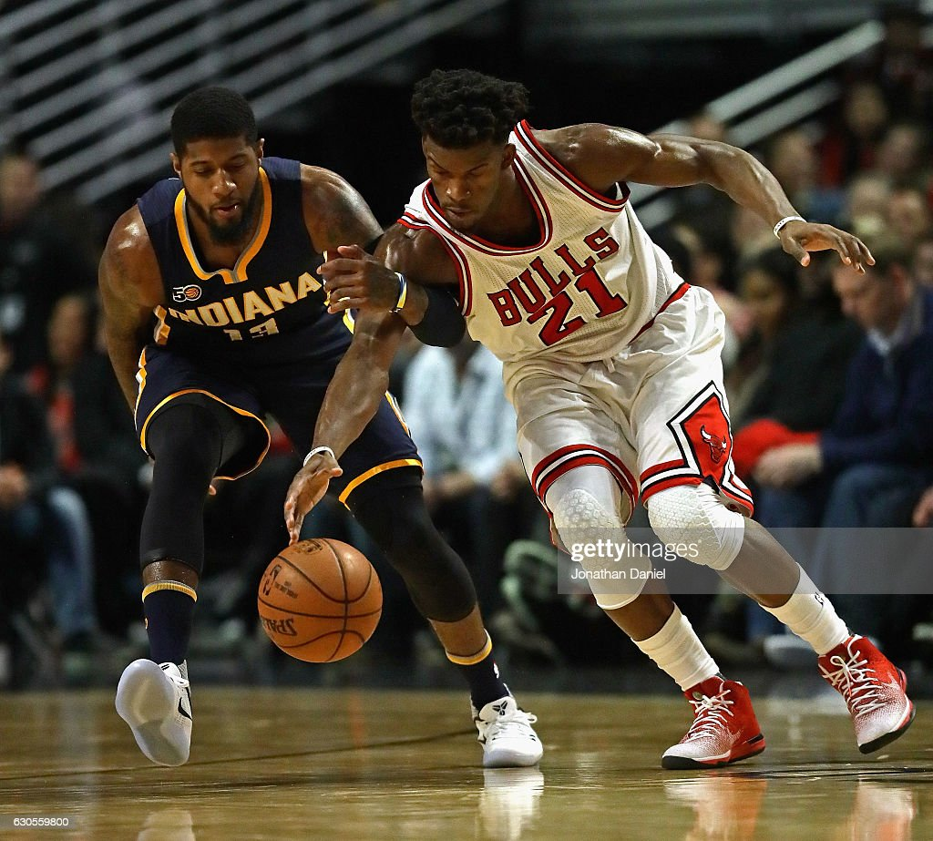 Jimmy Butler #21 of the Chicago Bulls and Paul George #13 of the Indiana Pacers chase down a loose ball at the United Center on December 26, 2016 in Chicago, Illinois.