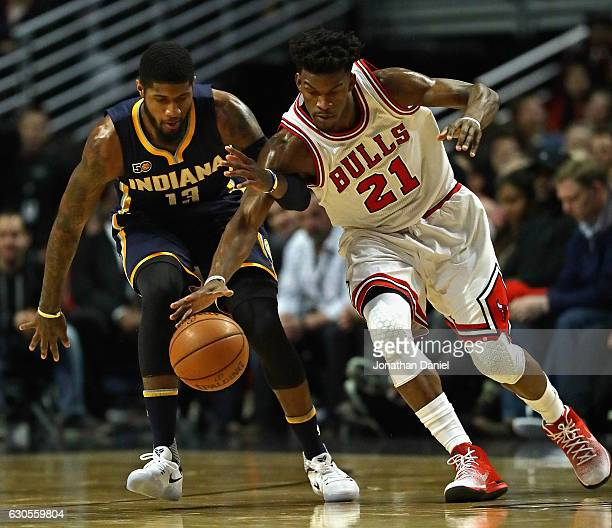 Jimmy Butler of the Chicago Bulls and Paul George of the Indiana Pacers chase down a loose ball at the United Center on December 26 2016 in Chicago...