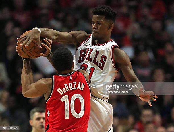 Jimmy Butler of the Chicago Bulls blocks a shot by DeMar DeRozan of the Toronto Raptors at the United Center on December 28 2015 in Chicago Illinois...