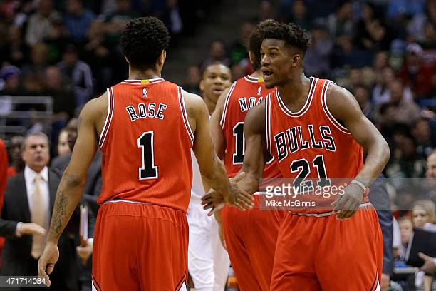 Jimmy Butler of the Chicago Bulls celebrates with Derrick Rose after shooting a three pointer in the first quarter against the Milwaukee Bucks in the...