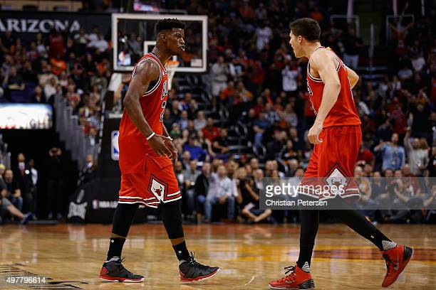 Jimmy Butler of the Chicago Bulls celebrates with Doug McDermott after scoring against the Phoenix Suns during the second half of the NBA game at...