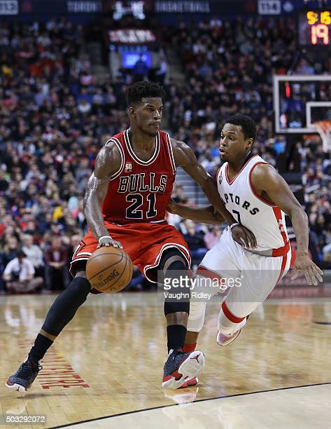 Jimmy Butler of the Chicago Bulls dribbles past Kyle Lowry of the Toronto Raptors defend during an NBA game at the Air Canada Centre on January 03...