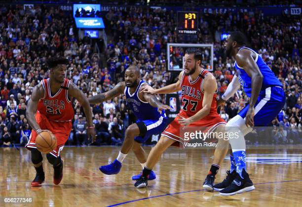Jimmy Butler of the Chicago Bulls dribbles the ball as teammate Joffrey Lauvergne PJ Tucker Patrick Patterson of the Toronto Raptors defend during...