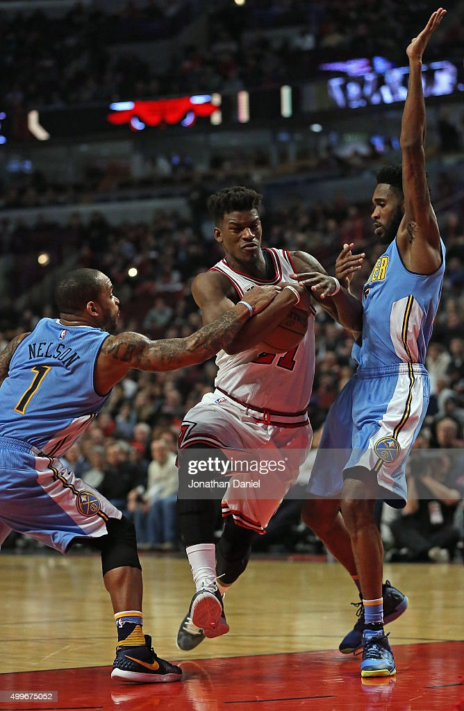 Jimmy Butler of the Chicago Bulls drives between Jameer Nelson and Will Barton of the Denver Nuggets at the United Center on December 2 2015 in...
