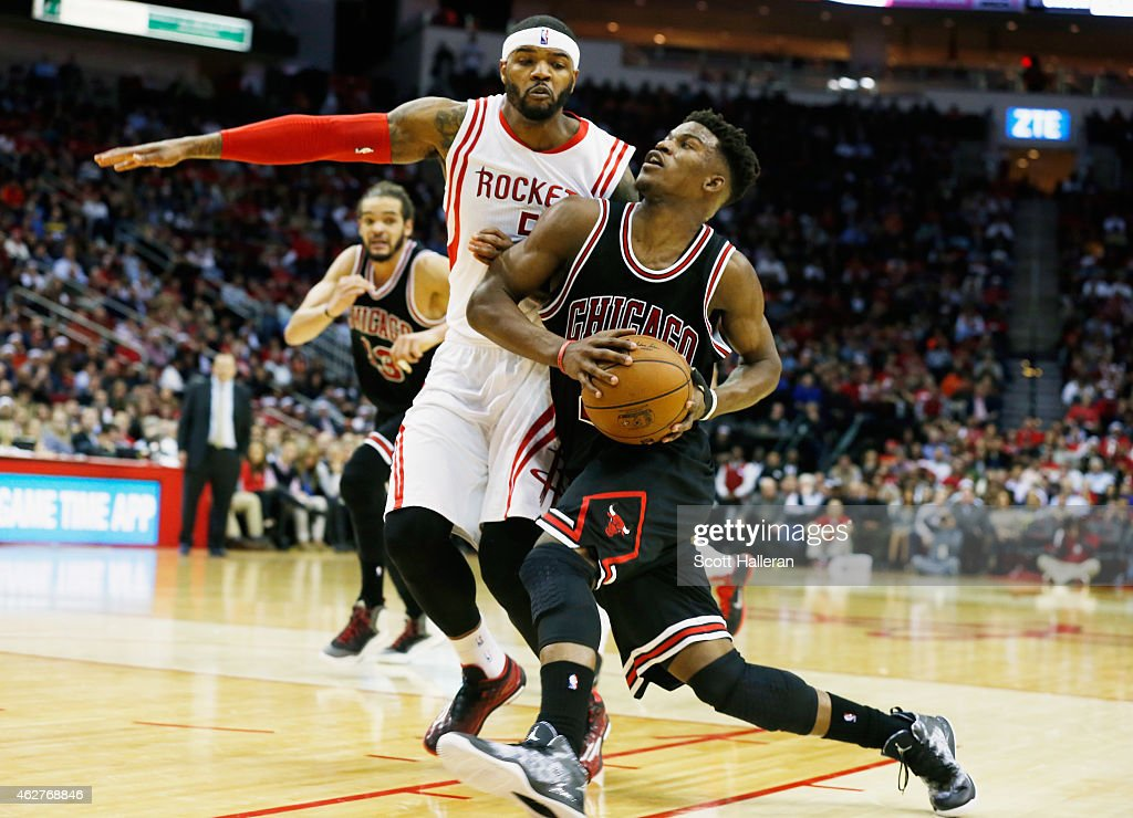 Jimmy Butler #21 of the Chicago Bulls drives with the ball against Josh Smith #5 of the Houston Rockets during their game at the Toyota Center on February 4, 2015 in Houston, Texas..