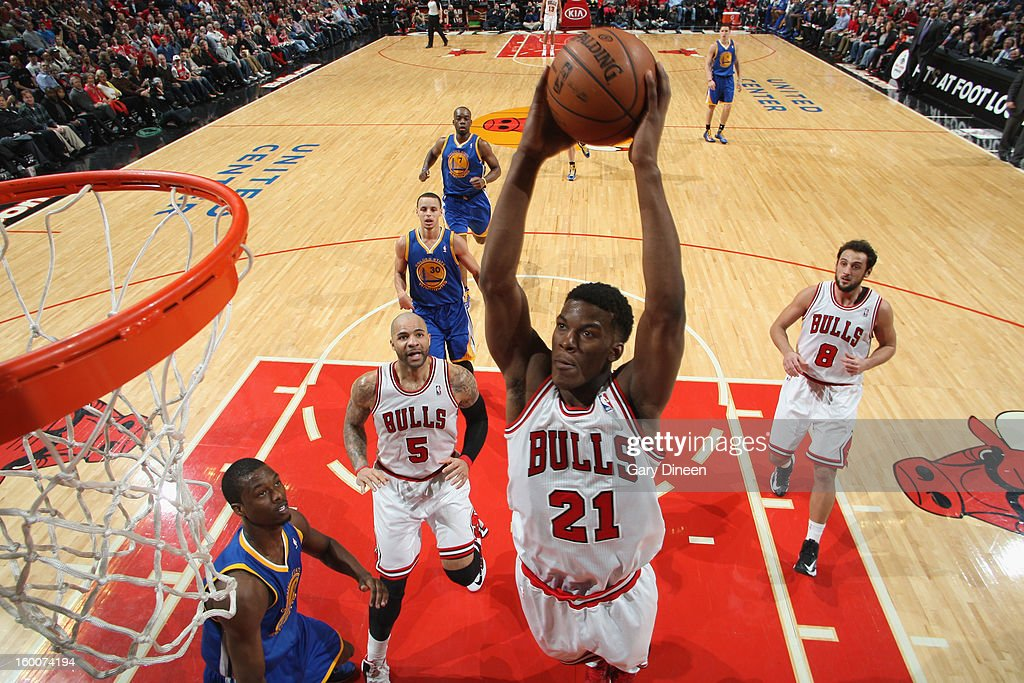 Jimmy Butler #21 of the Chicago Bulls dunks against Harrison Barnes #40 of the Golden State Warriors on January 25, 2012 at the United Center in Chicago, Illinois.