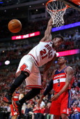 Jimmy Butler of the Chicago Bulls dunks over Bradley Beal of the Washington Wizards in Game One of the Eastern Conference Quarterfinals during the...
