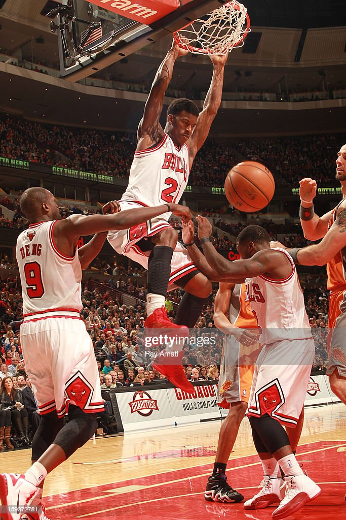 Jimmy Butler #21 of the Chicago Bulls dunks over teammates Marco Belinelli #8 and Nate Robinson #2 during the game against the Phoenix Suns on January 12, 2013 at the United Center in Chicago, Illinois.