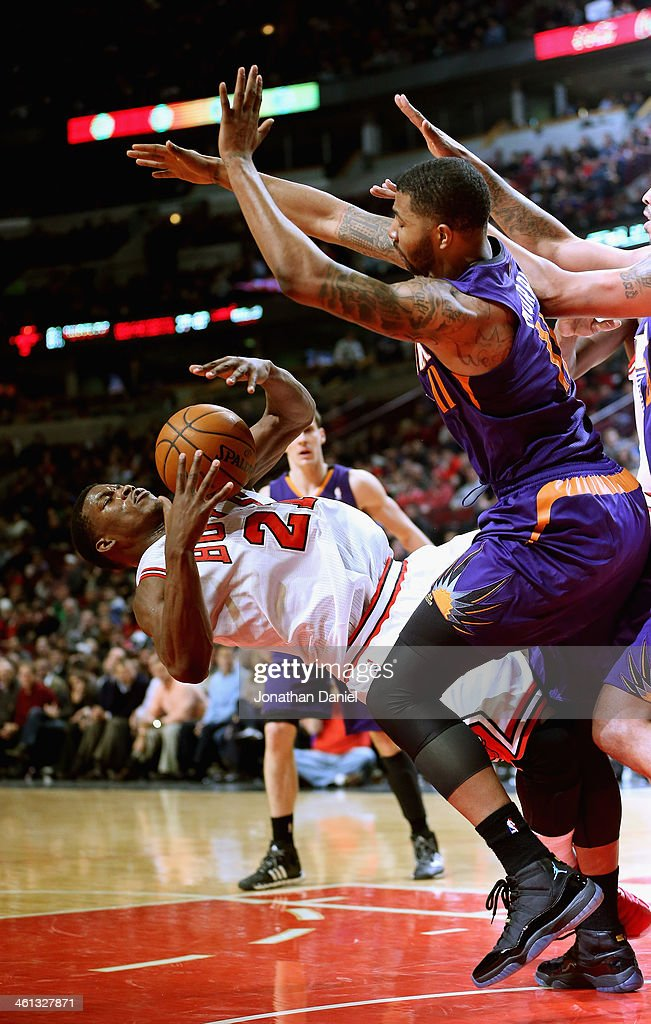 Jimmy Butler of the Chicago Bulls falls to the court after being fouled as Markieff Morris of the Phoenix Suns defends at the United Center on...