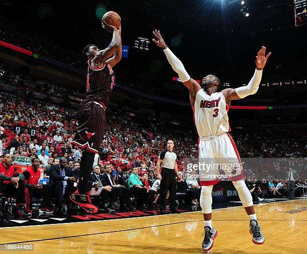 Jimmy Butler of the Chicago Bulls goes for a jump shot against Dwyane Wade of the Miami Heat during a game between the Chicago Bulls and the Miami...