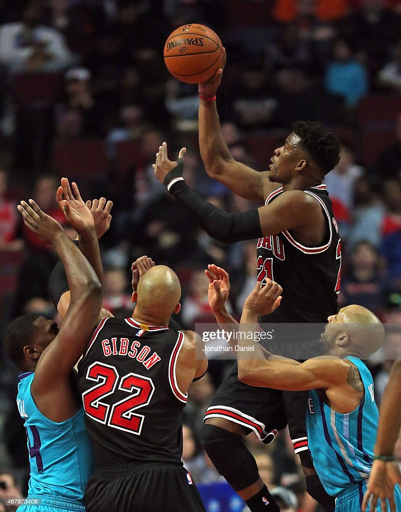 Jimmy Butler #21 of the Chicago Bulls goes up a shot over teammate Taj Gibson #22 and Michael Kidd-Gilchrist #14 and Gerald Henderson #9 of the Charlotte Hornets at the United Center on March 23, 2015 in Chicago, Illinois.