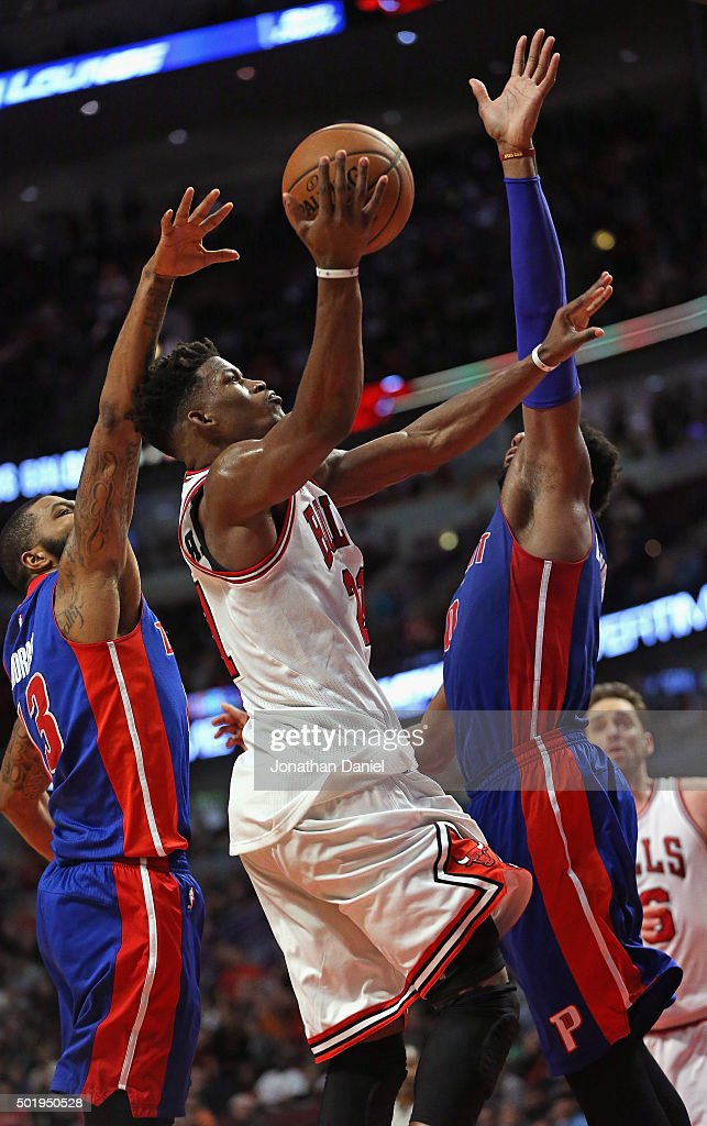 Jimmy Butler #21 of the Chicago Bulls goes up for a shot between Marcus Morris #13 (L) and Andre Drummond #0 of the Detroit Pistons on his way to a game-high 43 points at the United Center on December 18, 2015 in Chicago, Illinois. The Pistons defeated the Bulls 147-144 in quadruple overtime.