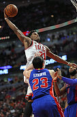 Jimmy Butler of the Chicago Bulls goes up for dunk over Ersan Ilyasova and Andre Drummond of the Detroit Pistons on his way to a gamehigh 43 points...