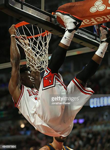 Jimmy Butler of the Chicago Bulls hangs on the rim after a dunk against the Cleveland Cavaliers during the season opening game at the United Center...
