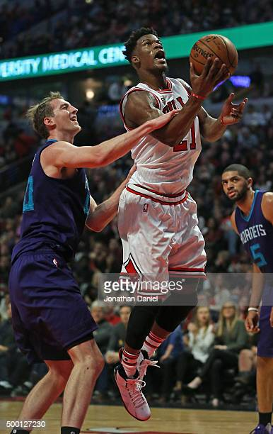 Jimmy Butler of the Chicago Bulls if fouled by Cody Zeller of the Charlotte Hornets at the United Center on December 5 2015 in Chicago Illinois The...