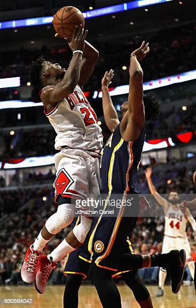 Jimmy Butler of the Chicago Bulls is fouled by Myles Turner of the Indiana Pacers at the United Center on December 26 2016 in Chicago Illinois The...