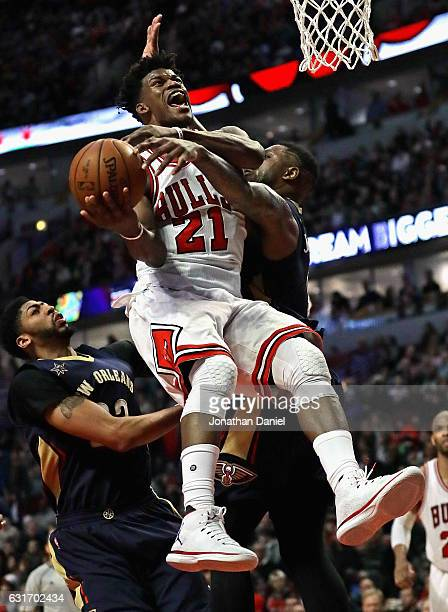 Jimmy Butler of the Chicago Bulls is fouled by Terrence Jones of the New Orleans Pelicans as he goes up for a shot past Anthony Davis at the United...