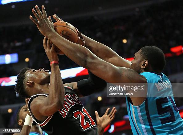 Jimmy Butler of the Chicago Bulls is fouled while shooting by Jason Maxiell of the Charlotte Hornets at the United Center on March 23 2015 in Chicago...