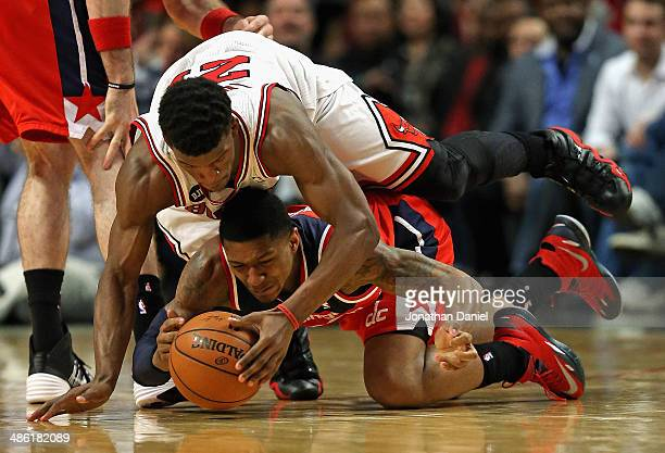 Jimmy Butler of the Chicago Bulls lands on top of Bradley Beal of the Washington Wizards as they battle for a loose ball in Game Two of the Eastern...