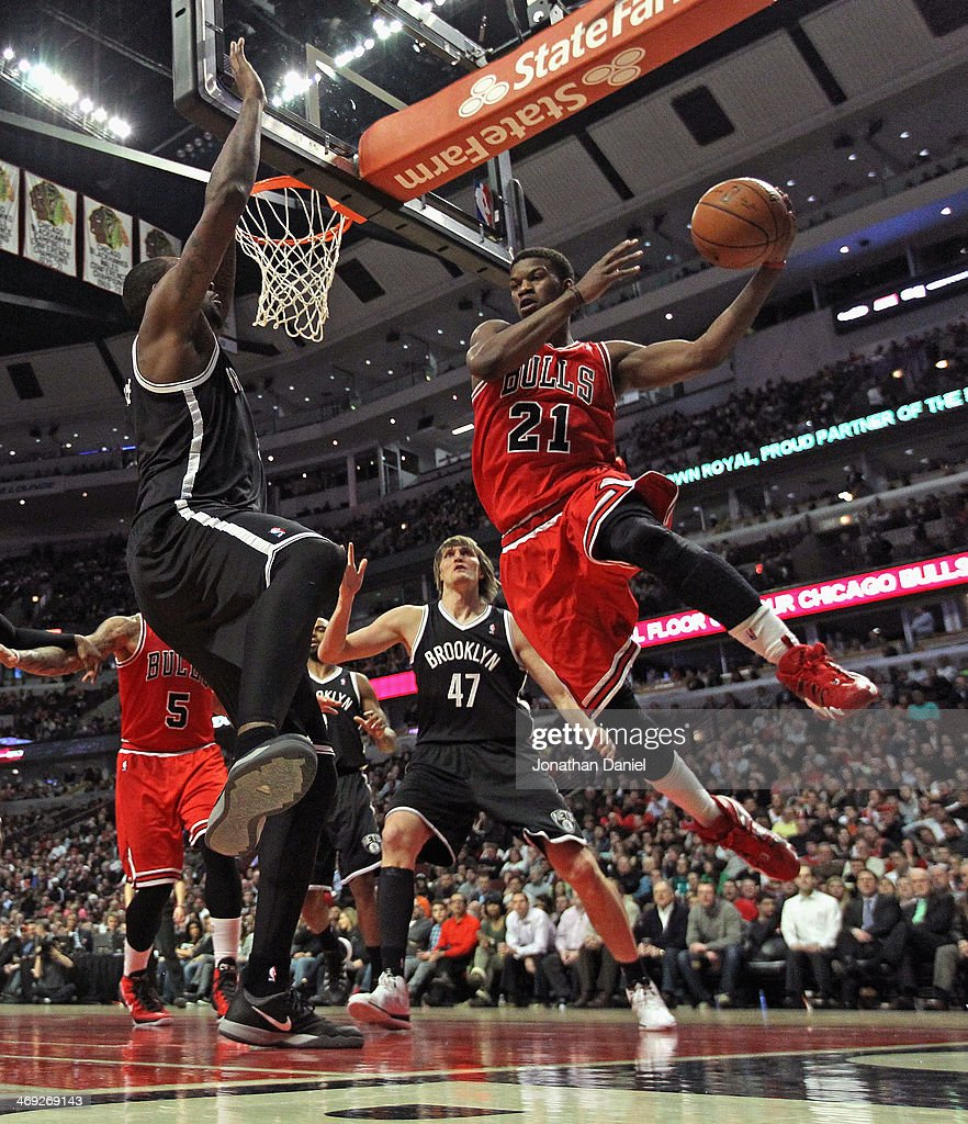 Jimmy Butler #21 of the Chicago Bulls leaps to pass around Andray Blatche #0 of the Brooklyn Nets at the United Center on February 13, 2014 in Chicago, Illinois. The Bulls defeated the Nets 92-76.