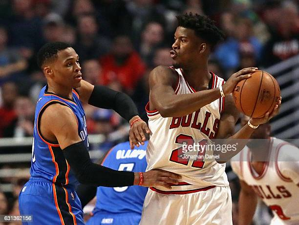 Jimmy Butler of the Chicago Bulls looks to pass against Russell Westbrook of the Oklahoma City Thunder at the United Center on January 9 2017 in...