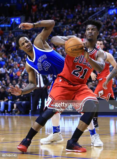 Jimmy Butler of the Chicago Bulls passes the ball as DeMar DeRozan of the Toronto Raptors defends during overtime of an NBA game at Air Canada Centre...