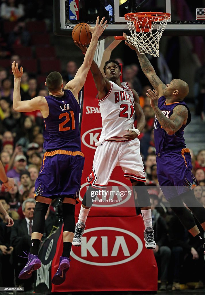Jimmy Butler #21 of the Chicago Bulls puts up a shot between Alex Len #21 and P.J. Tucker #17 of the Phoenix Suns at the United Center on February 21, 2015 in Chicago, Illinois. The Bulls defeated the Suns 112-107.
