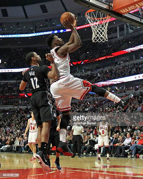 Jimmy Butler of the Chicago Bulls puts up a shot over Gary Neal of the Minnesota Timberwolves on his way to a gamehigh 28 points at the United Center...