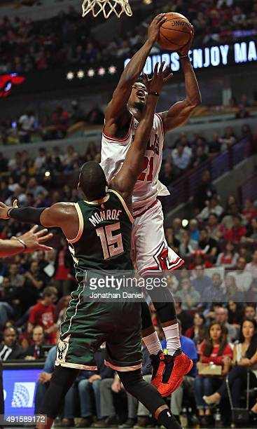 Jimmy Butler of the Chicago Bulls puts up a shot over Greg Monroe of the Milwaukee Bucks during a preseason game at the United Center on October 6...