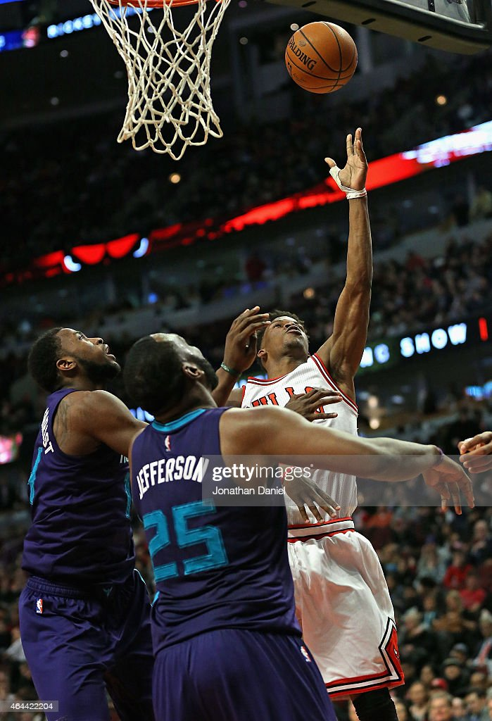 Jimmy Butler #21 of the Chicago Bulls puts up a shot over Michael Kidd-Gilchrist #14 and Al Jefferson #25 of the Charlotte Hornets at the United Center on February 25, 2015 in Chicago, Illinois. The Hornets defeated the Bulls 98-86.