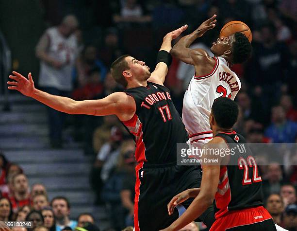 Jimmy Butler of the Chicago Bulls shoots against Jonas Valanciunas and over Rudy Gay of the Toronto Raptors at the United Center on April 9 2013 in...