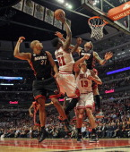 Jimmy Butler of the Chicago Bulls shoots between Shane Battier and Chris Anderson of the Miami Heat and Joakim Noah in Game Four of the Eastern...