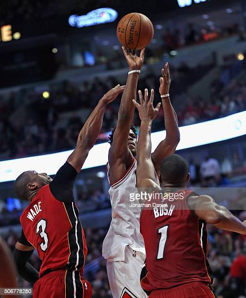 Jimmy Butler of the Chicago Bulls shoots over Dwyane Wade and Chris Bosh of the Miami Heat at the United Center on January 25 2016 in Chicago...