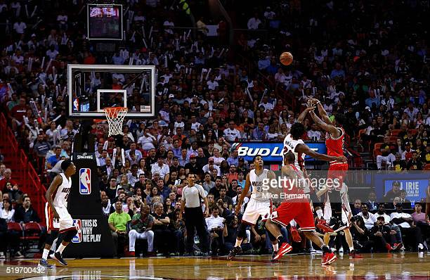 Jimmy Butler of the Chicago Bulls shoots over Justise Winslow of the Miami Heat during a game at American Airlines Arena on April 7 2016 in Miami...