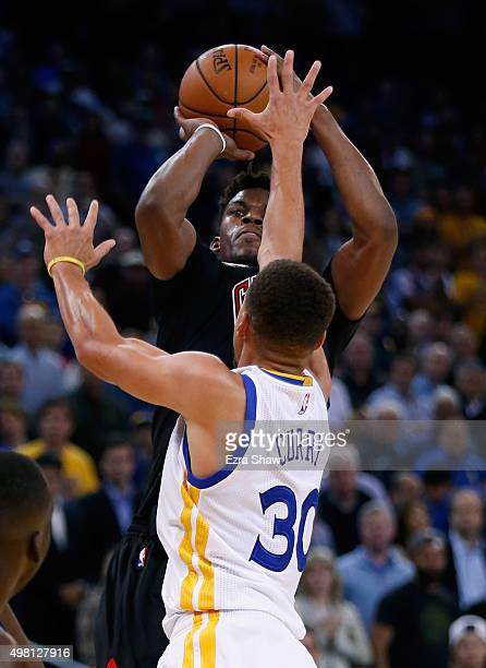 Jimmy Butler of the Chicago Bulls shoots over Stephen Curry of the Golden State Warriors at ORACLE Arena on November 20 2015 in Oakland California...