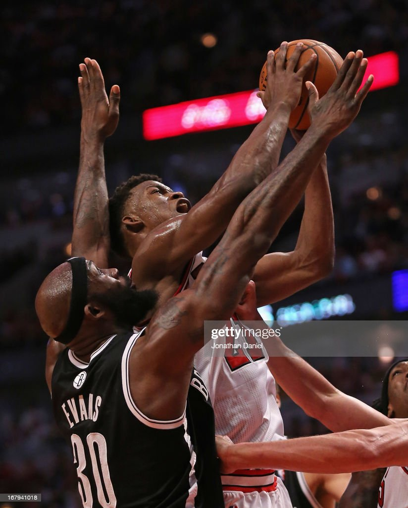 Jimmy Butler #21 of the Chicago Bulls shoots under pressure from Reggie Evans #30 of the Brooklyn Nets in Game Six of the Eastern Conference Quarterfinals during the 2013 NBA Playoffs at the United Center on May 2, 2013 in Chicago, Illinois. The Nets defeated the Bulls 95-92.