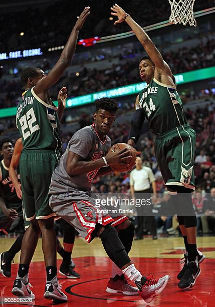 Jimmy Butler of the Chicago Bulls turns to pass under pressure from Khris Middleton and Giannis Antetokounmpo of the Milwaukee Bucks at the United...