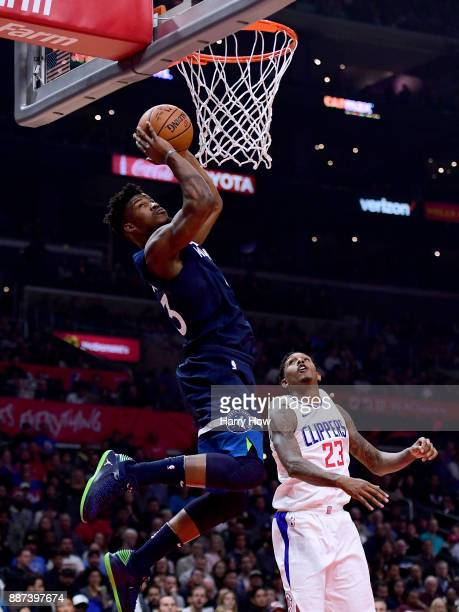 Jimmy Butler of the Minnesota Timberwolves scores on an alley in front of Lou Williams of the LA Clippers during the first half at Staples Center on...
