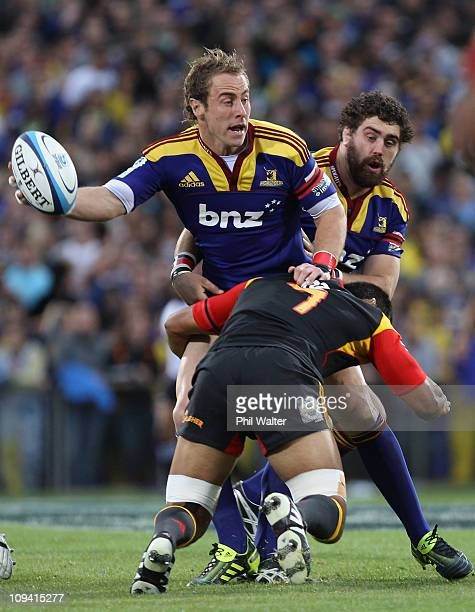 Jimmy Cowan of the Highlanders offloads the ball in the tackle of Tanerau Latimer of the Chiefs during the round two Super Rugby match between the...