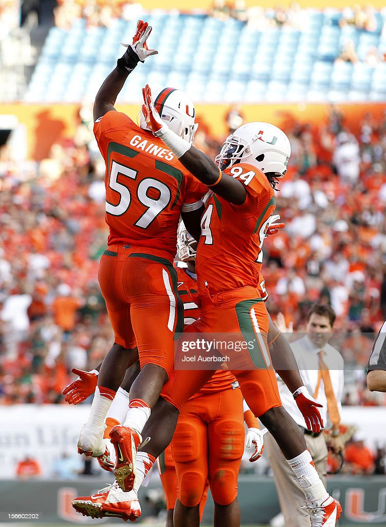 Jimmy Gaines #59 is congratulated by Kelvin Cain #94 of the Miami Hurricanes after scoring a touchdown against the South Florida Bulls on November 17, 2012 at Sun Life Stadium in Miami Gardens, Florida. The Hurricanes defeated the Bulls 40-9.
