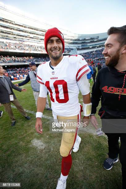 Jimmy Garoppolo and Administrative Assistant To The Head Coach Nick Kray of the San Francisco 49ers stand on the field following the game against the...