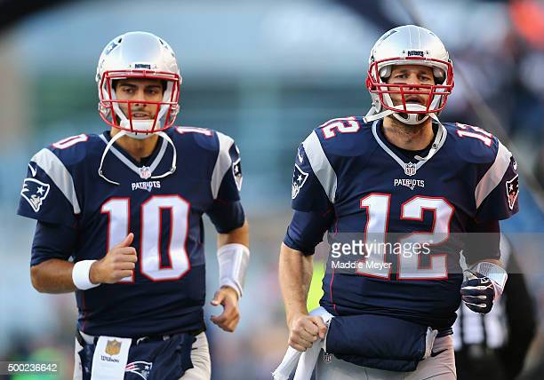 Jimmy Garoppolo of the New England Patriots and Tom Brady of the New England Patriots run onto the field prior to the game between the New England...