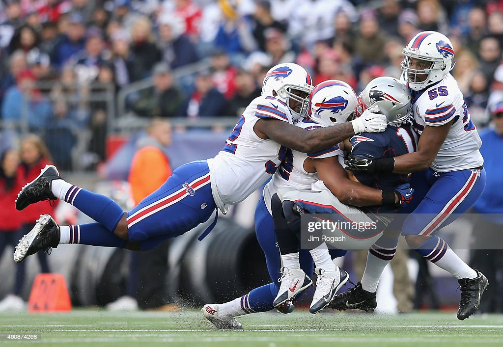 Jimmy Garoppolo #10 of the New England Patriots is tackled by Jerry Hughes #55 and members of the Buffalo Bills during the third quarter at Gillette Stadium on December 28, 2014 in Foxboro, Massachusetts.