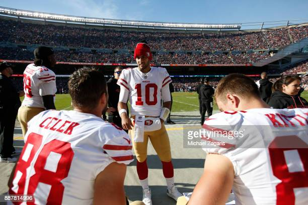 Jimmy Garoppolo of the San Francisco 49ers talks on the sideline with Garrett Celek and George Kittle during the game against the Chicago Bears at...